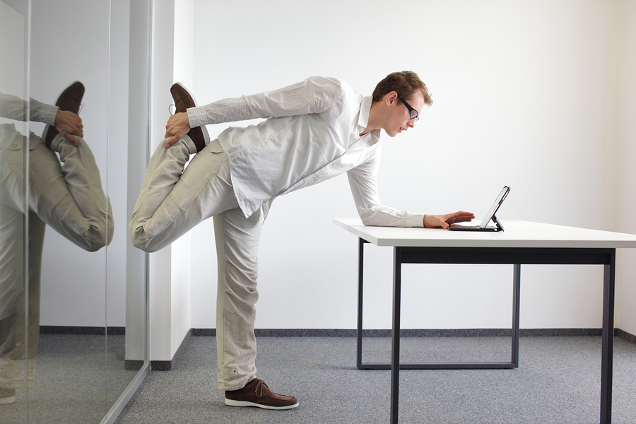 man doing leg exercises while working